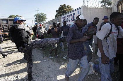 A U.N peacekeeper from Jordan kicks a Haitian man as they disperse people asking for food from around the airport in Port-au-Prince January 18th.