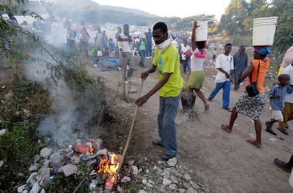 Yonel Regis, a pastor from a local church, burns trash at a refugee camp set up on a golf course in Port-au-Prince.