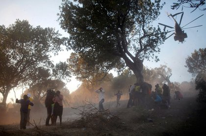 People cling to a tree as a U.S. helicopter, carrying disaster relief supplies, flies over a refugee camp in Port-au-Prince.