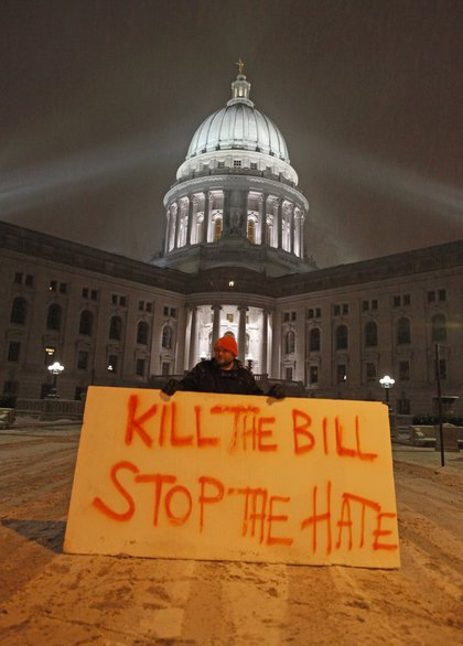 Luke Balsavich holds a large sign outside the state Capitol Monday.