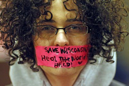 Kathryn Schulze wears a message written on tape over her mouth inside the state Capitol.