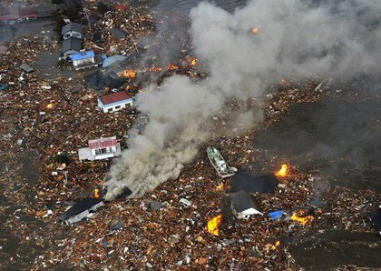 Flames rise from houses and debris half submerged in tsunami in Sendai, Miyagi Prefecture (state) after Japan was struck by a strong earthquake off its northeastern coast Friday, March 11, 2011.