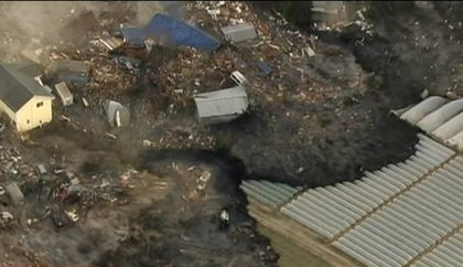 In this image from Japan's NHK TV video footage, houses are washed away by tsunami in Sendai, Miyagi Prefecture (state) eastern Japan, after Japan was struck by a magnitude 8.9 earthquake off its northeastern coast Friday, March 11, 2011.