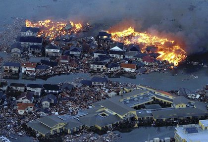 Houses are in flame while the Natori river is flooded over the surrounding area by tsunami tidal waves in Natori city, Miyagi Prefecture, northern Japan, March 11, 2011, after strong earthquakes hit the area.
