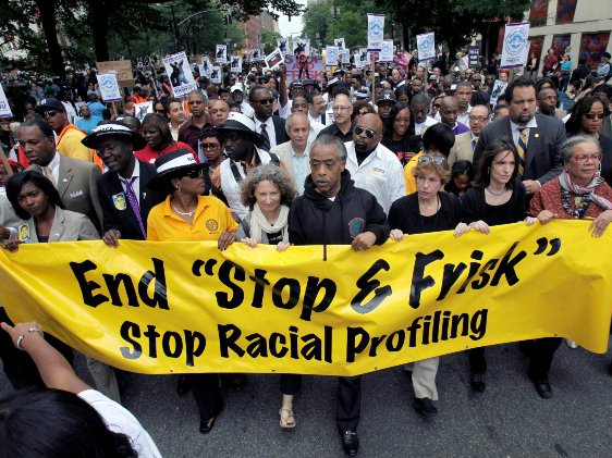 "The Rev. Al Sharpton, center, walks with demonstrators during a silent march to end New York's ""stop-and-frisk"" program in 2012."