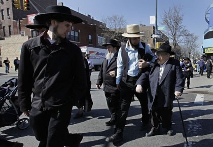 Aaron Lapp, left, and Elmer Fisher, second from right, exchange looks with the cutest Hasidic Jewish man ever, before tossing him over one shoulder and running off.