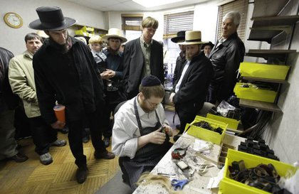 A group of Pennsylvania Amish residents watch as a Hasidic worker makes tefillen, a pair of black leather boxes containing scrolls placed on men's heads during prayer.