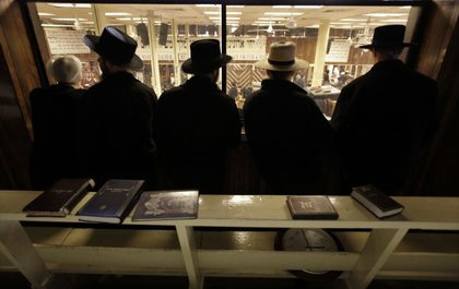 A group of Amish visitors get a view of the men's section of a synagogue from the women's section above.