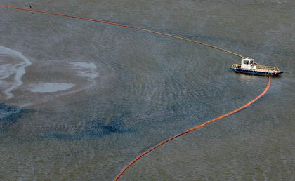 A clean-up boat lays out oil booms along Port East in the Gulf of Mexico south of Louisiana.