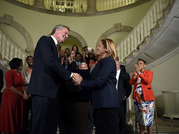 Mayor de Blasio and Speaker Melissa Mark-Viverito shaking hands on the FY 2018 Budget in June. When this photo was taken, no agreement had been reached on immigrant defense funding.