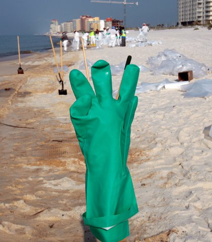 A rubber glove sits on the end of a shovel handle as oil cleanup workers scour the sand in Orange Beach, Ala., Monday, June 14, 2010. Much of the thick oil from the Deepwater Horizon spill has been cleaned up, but a dark stain remains behind.