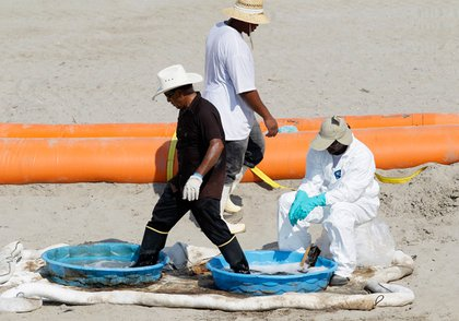 A worker washes his his boots after cleaning up oil from the Deepwater Horizon oil spill on the beach, Monday, June 14, 2010, in Grand Isle, La.