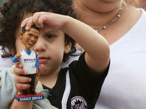 """Barak Landis, 3, plays with his Obama bobble head as his mother Judy holds him during the """"Baracklyn"""" Cyclones game last night."""