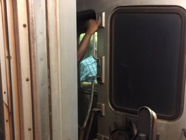 A person rides between cars on the 1 train during Monday's morning commute meltdown.