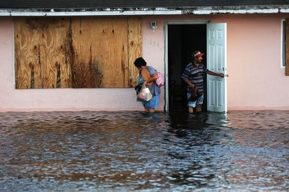 A couple leave their flooded home the morning after Hurricane Irma swept through the area on September 11, 2017 in Fort Myers, Florida. (Getty)
