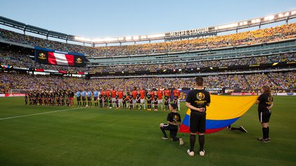Starters for Colombia and Peru stand during pre-match ceremonies.