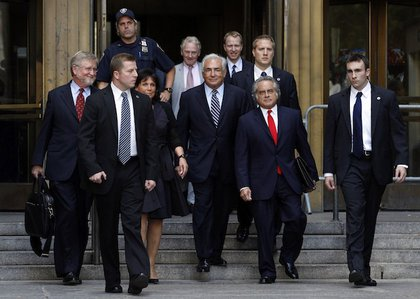 Dominique Strauss-Kahn, his wife Anne Sinclair, and his defense team exit the courthouse.