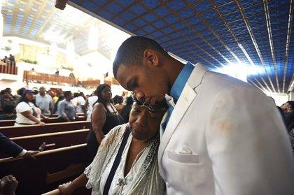 Gwen Carr, mother of Eric Garner, and Eric Snipes Garner, Jr., son of Eric Garner, hug after the funeral<br/>