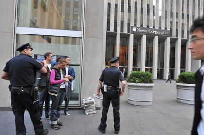 Police detain volunteers distributing free copies of the fake New York Post outside News Corp. headquarters.