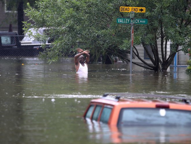 A man waves down a rescue crew as he tries to leave the area after it was inundated with flooding from Hurricane Harvey on August 28, 2017 in Houston, Texas<br>