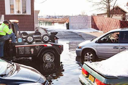A waterlogged van is pulled from 160th Avenue in Howard Beach<br/>