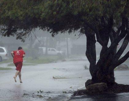 A man runs down a street as Hurricane Matthew moves through Daytona Beach (AP)