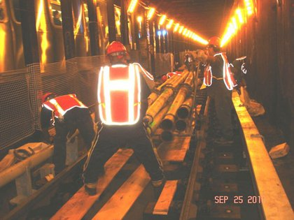"""Track Workers installing 5"" concrete pipe that gets concrete from street to the track @ 34th St (E)."""