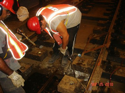 """Track Workers chipping out concrete for installation of new roadbed along local track near 34th St (E)."""