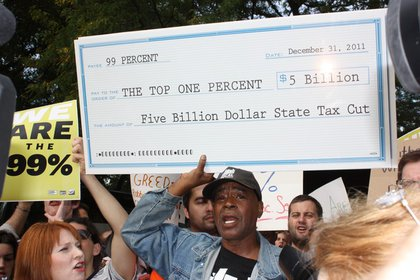 A protester displays the amount of money that will be lost in tax revenue if the Millionaire's Tax isn't renewed