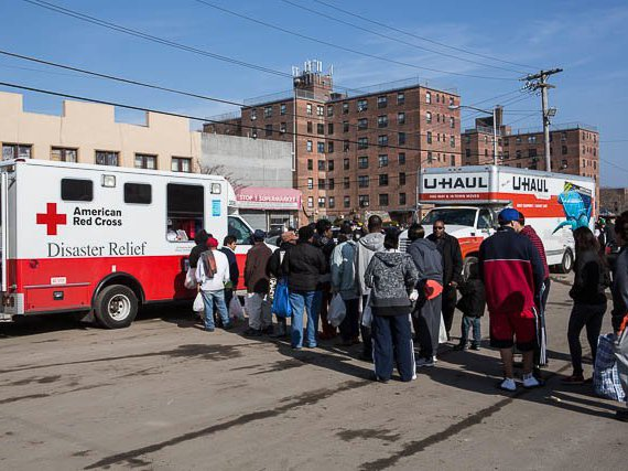 Residents in Rockaway Beach line up for lunch at a Red Cross truck