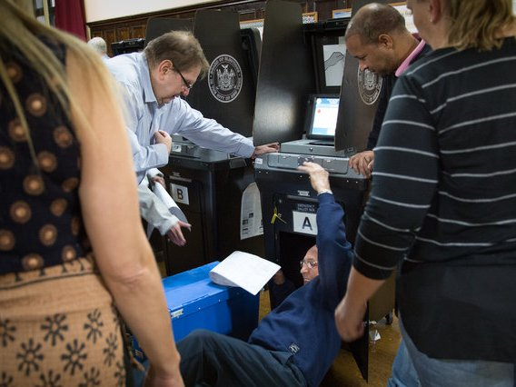BOE workers try and fix a broken scanner on Election Day 2018