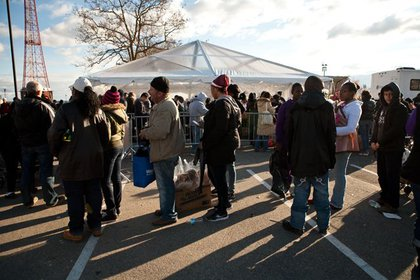 Residents wait for food and supplies outside a FEMA tent