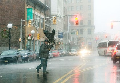A man's umbrella flips from the strong wind as he crosses Sip Avenue on Journal Square in Jersey City.