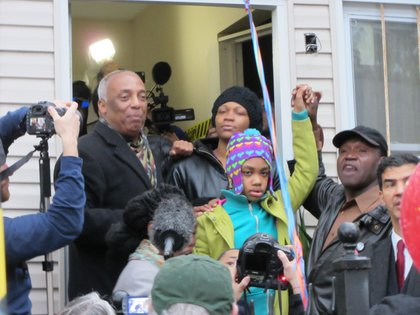 Alfredo Carrasquillo's daughter outside the house with her mother Tasha Glasgow and Council Member Charles Barron.