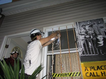 A volunteer puts up Christmas lights on the house.
