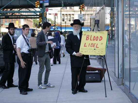 "A photo of a man holding a ""Blood Libel"" sign during a heated circumcision hearing in 2013"