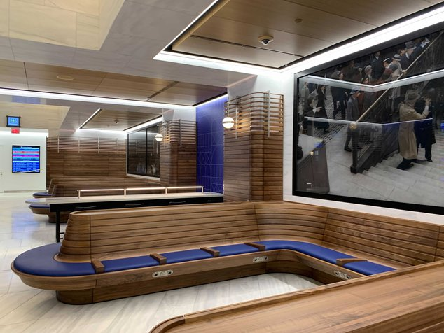 A luxurious new train lounge with lots of wood and comfortable cushions.