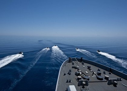 ) Rigid hull inflatable boats get in formation in front of the amphibious transport dock ship USS New York
