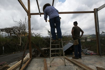 Men work repairing a partially destroyed bar three weeks after Hurricane Maria hit the island, on October 11, 2017 in Aibonito, Puerto Rico. <br/>