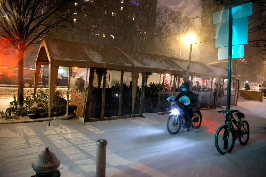 A delivery cyclist rides through the snow next to a shuttered outdoor dining setup in the East Village during last month's snowstorm.