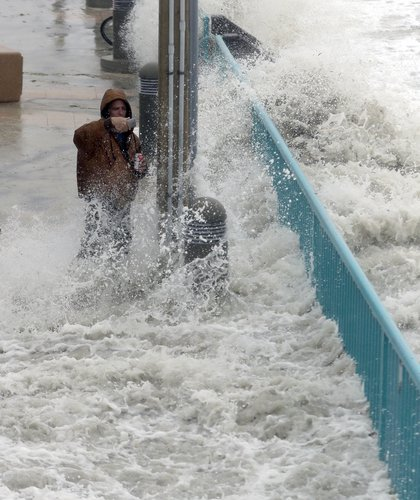 Brian Johns is hit by a wave as he tries to video the effects of Hurricane Matthew, Friday, Oct. 7, 2016, in Daytona Beach (AP)