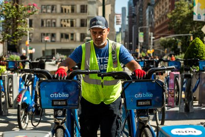 Citi Bike Senior Driver Ed Avilez removes two bikes from the racks at Broadway and West 24th Street in Flatiron, Manhattan. The Citi Bike docking station will soon move across 24th Street to free up pedestrian space.</br>