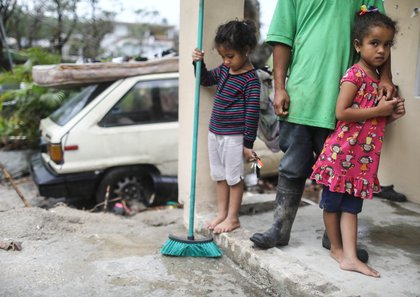 Young members of the Timoral family stand in front of their damaged home, with no running water or electricity, more than two weeks after Hurricane Maria hit the island, on October 9, 2017 in Jayuya, Puerto Rico. <br/>