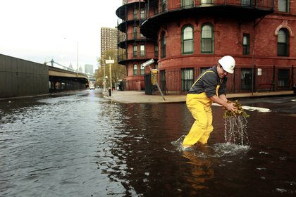 A man clears leaves from a sewer drain in lower Manhattan. <br/>