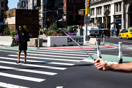 A woman uses a new 24th Street crosswalk to cross Broadway. Department of Transportation officials installed the new walkway after closely studying the intersection and finding that thousands of pedestrians each day would venture into traffic and cross at the intersection, despite the previous lack of a signal and crosswalk.</br>