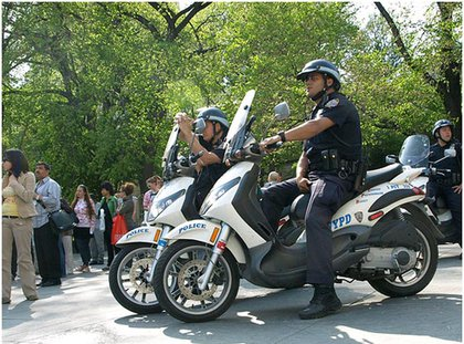 NYPD cops wait and watch from scooters.