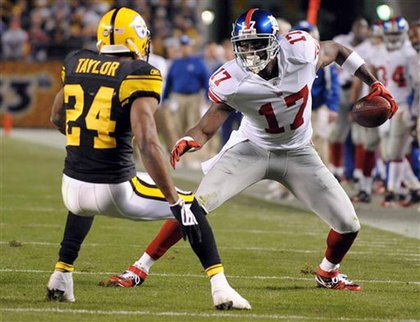 The Steelers' Ike Taylor  closes in as Giants wide receiver Plaxico Burress.