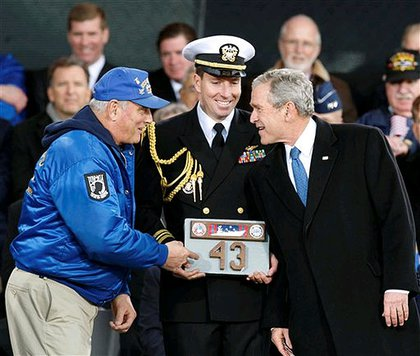 President Bush speaks to Mike Hallahan, president of the Intrepid Former Crew Members Association, while a naval attendant holds a piece of the deck of the Intrepid given as a gift to President Bush