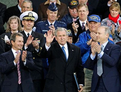 President Bush surround by veterans and veterans families.  At left is Intrepid Museum co-chairman Richard Santulli, and co-chairman Charles de Gunzberg is at right.