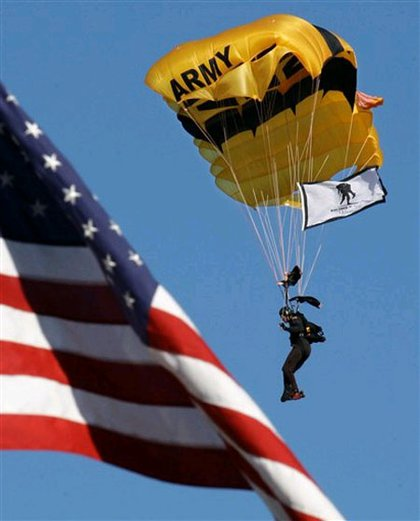 A member of the Army Black Knights parachutes past an American flag as part of the rededication ceremony